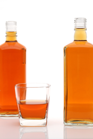 Glass cup and bottle of whiskey on white background 写真素材