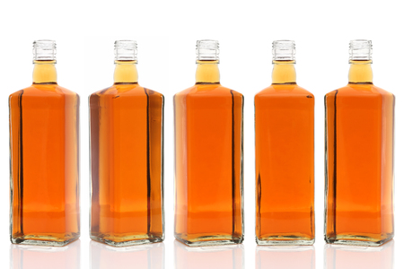 Row of glass bottle whiskey on a white background Stock Photo