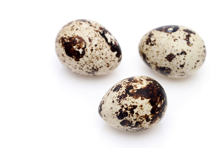 Three quail eggs on white background Zdjęcie Seryjne