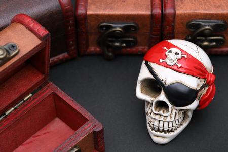 Skeleton pirate with treasure chest on dark background