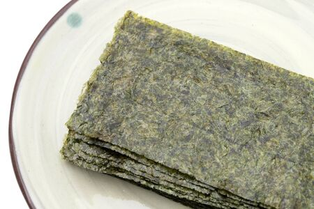 Japanese food, Nori dry seaweed sheets on plate Imagens