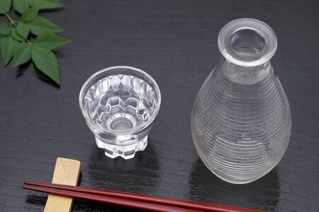 Japanese sake in transparent glass cup and jar