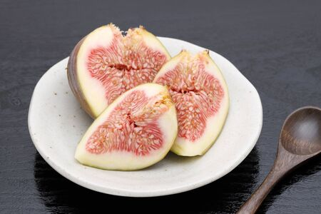 Ripe sweet fig on a plate on black background