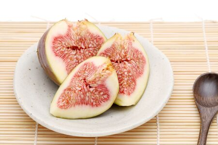 Ripe sweet fig on a plate on bamboo background Stock Photo