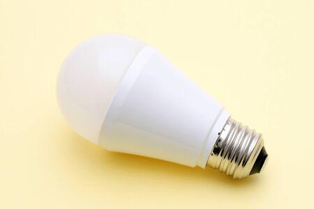 LED energy saving bulb on yellow background