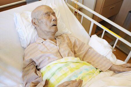 Patient japonais âgé allongé dans son lit en train de dormir Banque d'images