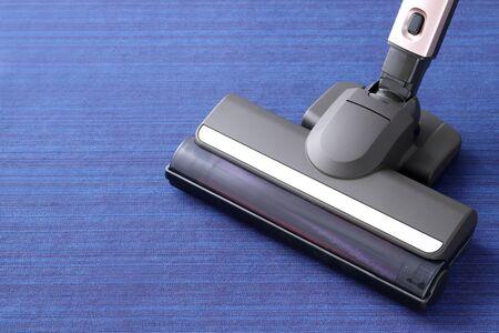 Head of modern vacuum cleaner on blue carpet Stock Photo