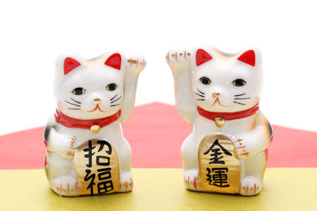 """Japanese lucky cat on white background, Japanese word of this photography means """"blessing, economic fortune"""""""