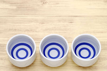 Japanese sake in traditional ceramic ochoko cup on wooden table