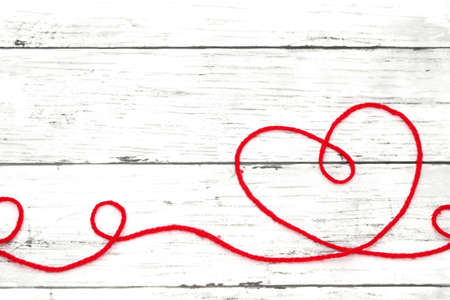 Red woolen thread in the shape of heart on white wooden table