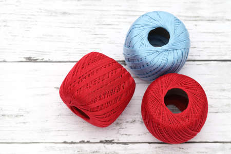 Ball of red and blue threads on white wooden table