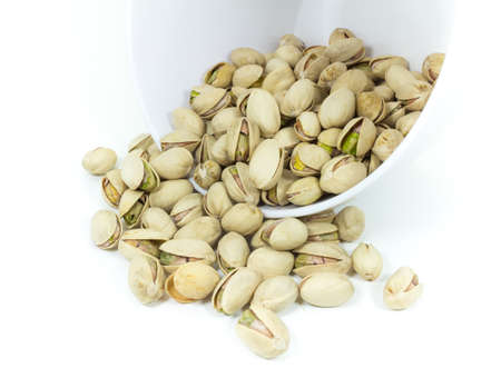 pistachios: Pistachios nuts spilling out of the bowl