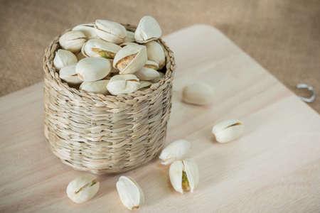 wooden block: Salty pistachios nuts on rustic wooden block