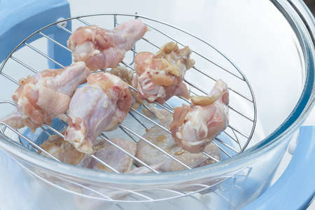 oven chicken: Fresh chicken drumstick in the electric oven Stock Photo