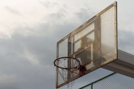 Basketball backboard against the stormy sky background and a little sunny ray to the hoopdark theme