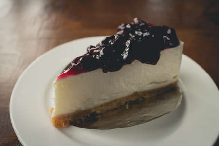 cheese: Cake with cream cheese and blueberries. selective focus, filtered image processed vintage effect.