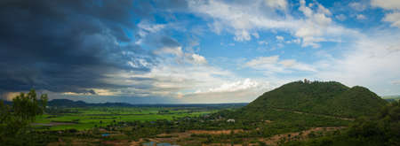 strom: Thailand landscape of rural city and moutain under the blue sky but the strom is coming. Stock Photo