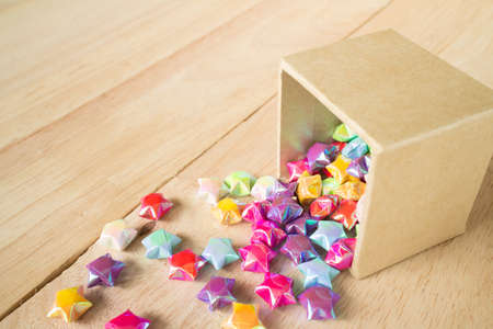 paper fold: colorful of paper fold christmas stars spilling out from the paper box to wood surfaceselective focus