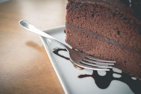 shiver: Piece of chocolate cake with warm chocolate syrupsoft focus and fade effect of vintage style