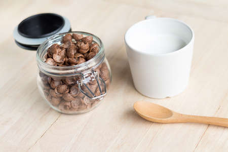 chocolate cereal: milk and chocolate cereal cornflakes in white cup that ready for serving in breakfast time