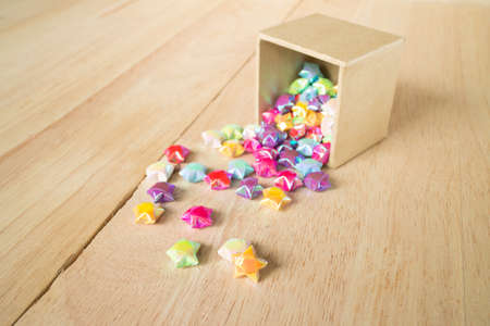 paper fold: colorful of paper fold christmas stars spilling out from the paper box to wood surface(soft focus)