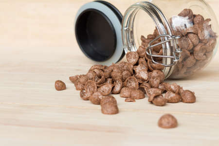 chocolate cereal: Chocolate cereal cornflakes spilling out from the glass jar