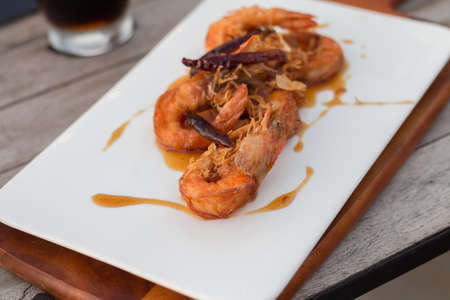 thai food: Deep fired shrimps serve with sweet fruit sauce in the cozy outdoor restaurant (soft focus) Stock Photo