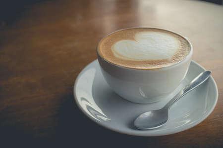 caffè caldo con schiuma di latte arte d'amore (effetto vintage)