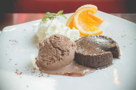 sliced orange: chocolate lava cake set with ice cream and sliced orange on white plate