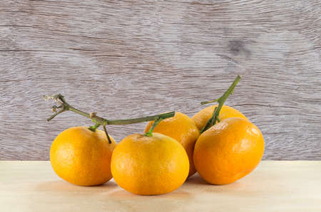 oranges on the wooden table on the abstract wood texture
