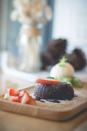 chocolate lava cake with vamilla ice cream and strawberry. chocolate lava on wood plate. chocolate lava. Hot chocolate pudding with fondant centre.(vintage, selective focus)