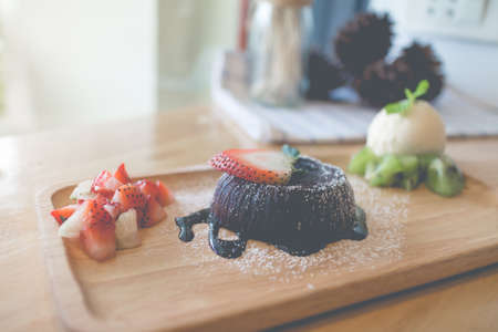 chocolate lava cake with vanilla ice cream and strawberry. chocolate lava on wood plate. chocolate lava. Hot chocolate pudding with fondant centre.(vintage, selective focus) Stock Photo