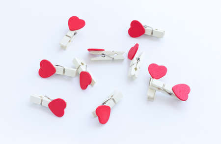 wooden clothes pin or cloth pegs with heart shape design on a white background Stock Photo