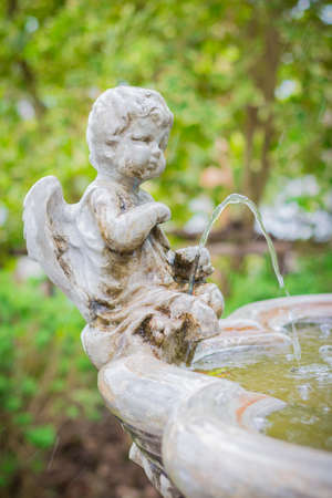 Statue of a beautiful little angle in the garden