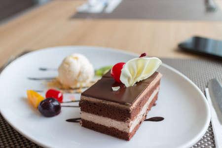 chocolate layer cake and vanilla ice cream with fresh fruit and cherry