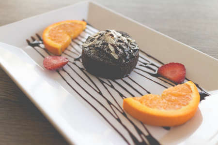 chocolate cake or chocolate lava cake with fresh fruit and coffee