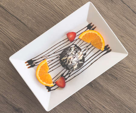 chocolate cake or chocolate lava cake with fresh fruit and coffee Stockfoto