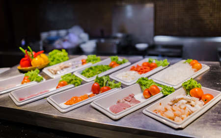 Picture of shrimps, pork, beef and salmon on grill station for buffet line
