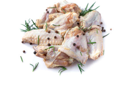 Raw chicken wings with garlic, pepperand rosemary isolated on white background