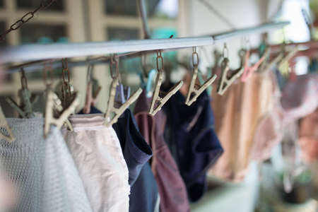 Clothes pegs or clothespins is hanging the underware on a cord. Plastic clothes pegs on a washing line Stockfoto