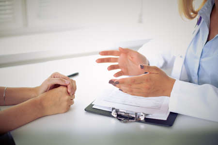 doctor office: Doctor and patient are discussing something, just hands at the table