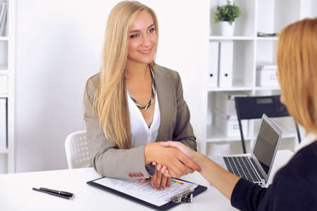 Cheerful  businesswoman and client handshaking, sitting at the table Foto de archivo