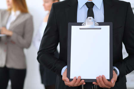 space   area: Unknown businessman holds clipboard with copy space area