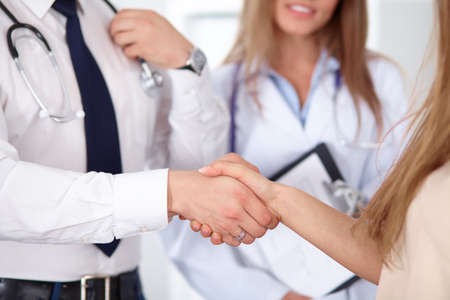 Friendly male doctor and female patient shaking hands. Partnership, trust and medical ethics concept. Standard-Bild