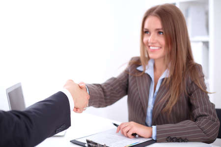 office background: young business woman handshaking  sitting at the desk on office background, copy space area at the left upper corner Stock Photo