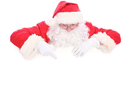 Kind Santa Claus looking out from behind the blank sign isolated on white background with copy space Foto de archivo