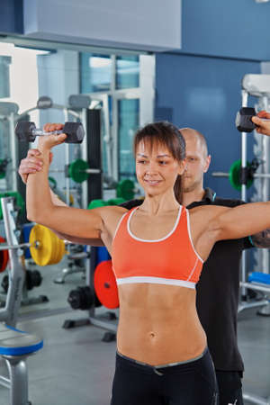 muscular body: Woman with Personal Trainer in Gym, blured background Stock Photo