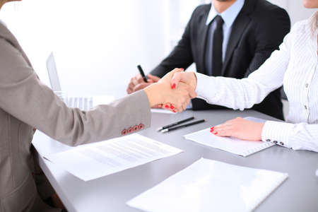 unanimous: Business people shaking hands, finishing up a meeting. Copy space  at the left corner