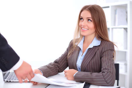 finance report: Young business woman is taking finance report sitting at the table against the background of the office Stock Photo