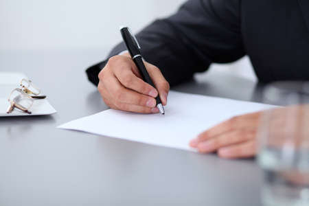 documentos: Primer plano de manos de los hombres con la pluma sobre el documento, concepto de negocio